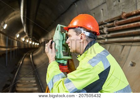 Surveyor with theodolite level at underground railway tunnel construction work