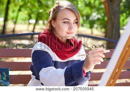 The femae artist paints a picture in the sunny day in a good mood. Young woman drawing a picture in autumn park.