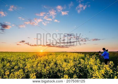 Landscape during the sunset against the background of a beautiful sky with clouds and a red sun over a rapeseed field. Man taking pictures of the landscape