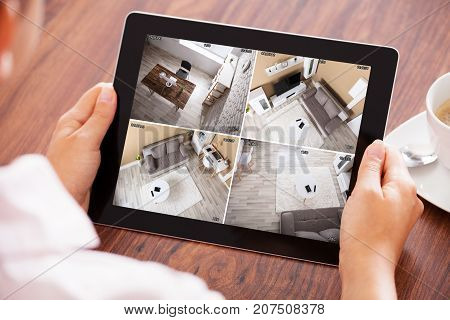 Elevated View Of A Person's Hand Looking At Home Security Cameras On Tablet