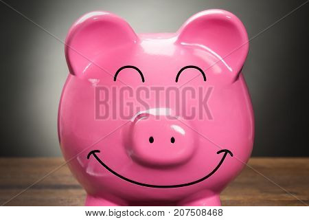 Close-up Of A Smiling Pink Piggybank On Wooden Table