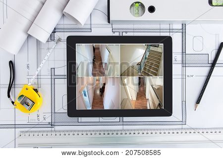 High Angle View Of Blueprint With CCTV Footage Of Office On Digital Tablet