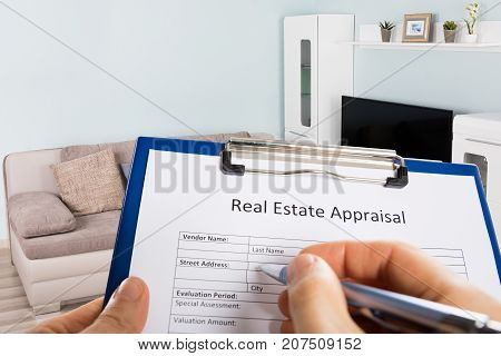 Close-up Of A Person's Hand Filling Real Estate Appraisal Form With Pen At Home