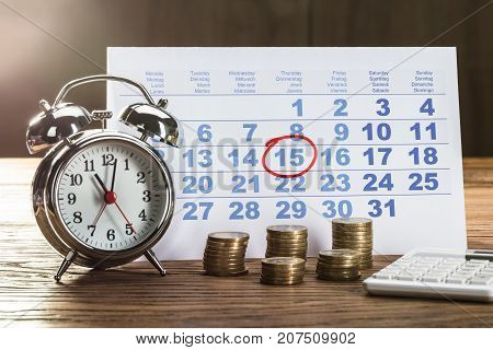 Red Circle Marked On Calendar With Clock And Coins Stack On Wooden Desk