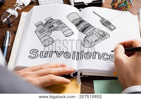 Close-up Of Person Drawing Surveillance Equipments In Book With Pen