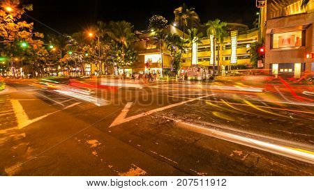 HONOLULU, OAHU, HAWAII, USA - AUGUST 21, 2016: cars crossing the Kalakaua Ave and Seaside Ave crossroad in motion blur with streets lights. Urban nightlife fun and shopping concept.