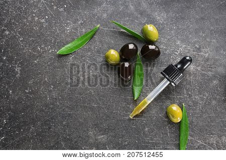 Pipette with olive oil on dark background