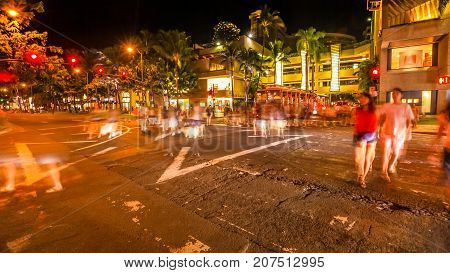 tourists people crossing the Kalakaua Ave and Seaside Ave crossroad in motion blur with streets lights. Urban nightlife fun and shopping concept. HONOLULU, OAHU, HAWAII, United States.