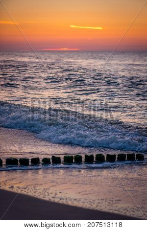 Old wooden breakwaters on the Baltic coast beach photographed at sunset