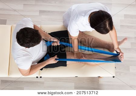 Female Therapist Assisting Male Patient While Stretching His Leg In Hospital