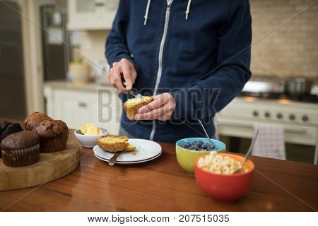 Mid-section of man preparing muffins in the kitchen