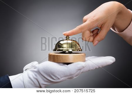 Customer Ringing Service Bell Held By Customer In Front Of Grey Background