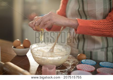 Mid section of woman breaking an egg Into bowl