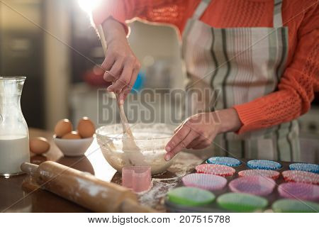 Mid section of woman mixing eggs and wheat flour in a bowl