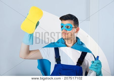 Young Male Superhero Janitor In Cape Wiping Glass