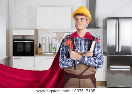 Repairman Daydreaming In Red Cape Holding Worktools In Kitchen