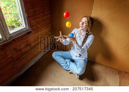 beautiful young smiling woman sitting and juggling