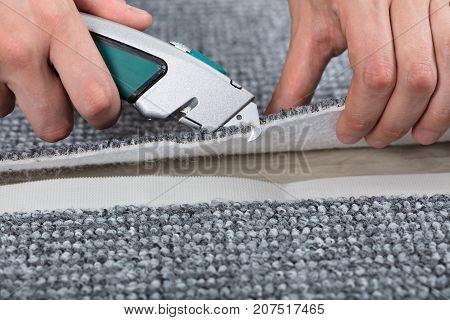 Carpenter Shaping Carpet Using Carpenter Tools To Lay Carpet At Home