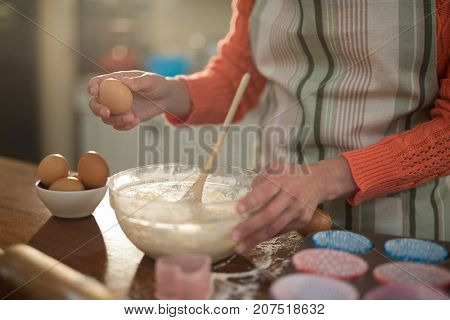Mid section of woman preparing cookies in kitchen