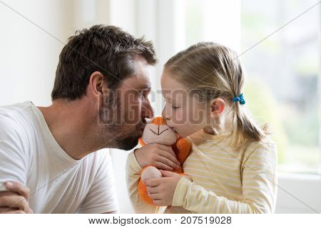 Father and daughter kissing soft toy at home