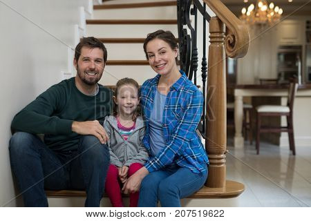 Parents and daughter sitting on stairs at home