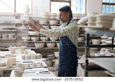 Male potter checking craft product in workshop