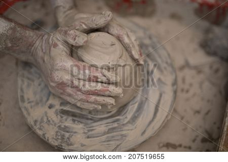 Close-up of male potter molding a clay in pottery workshop