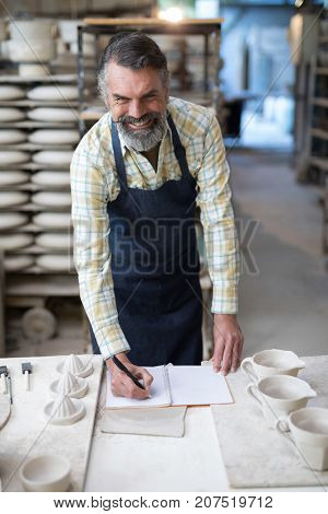 Portrait of male potter checking the orders in notebook