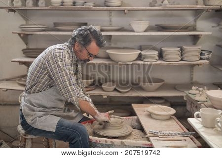 Male potter molding a clay in pottery workshop