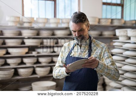 Male potter checking plate in pottery workshop