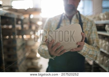 Mid section of male potter holding bowl in pottery workshop