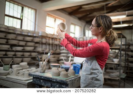 Woman checking mugs at worktop in pottery workshop