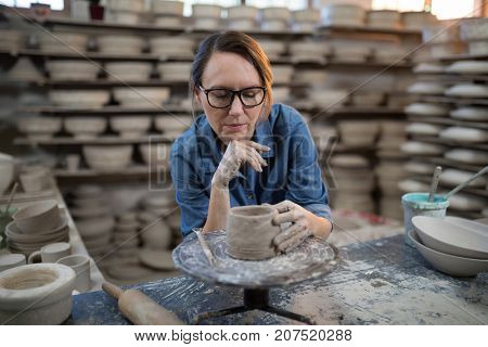 Female potter molding a clay in pottery workshop