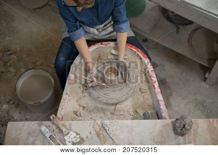 Overhead of female potter molding a clay in pottery workshop