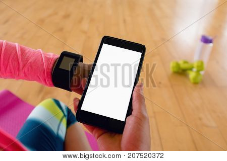Woman holding mobile hone while using smartwatch in the gym
