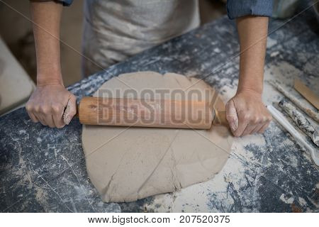 Mid section of female potter flattening the clay with rolling pin