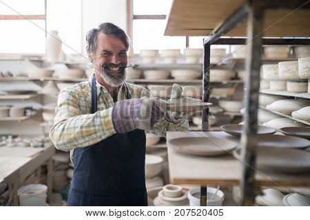 Happy male potter placing plate ob shelf in pottery workshop
