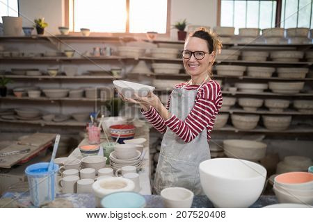 Portrait of female potter holding bowl in pottery workshop