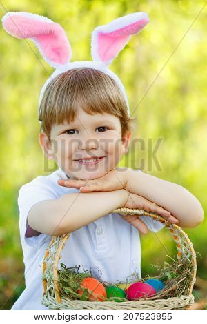 Easter bunny. Child with a basket of Easter colorful eggs. Kid, boy in a rabbit costume smiles.