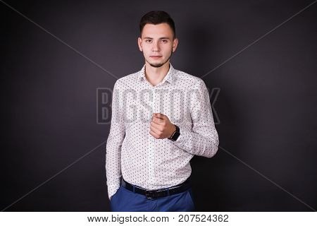 Successful business man in white shirt and black fashionable clock. Stylish man. Young man in a classic shirt. A successful man looks at the camera. Purposeful business man