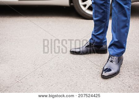 A man in black elegant shoes against the background of the car. Stylish shoes. Classic shoes on the asphalt. Business men in leather shoes