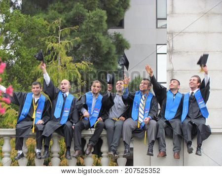 Berkeley USA, 15 May 2011: College students tossing their hats sitting on a wall wearing academic regalia dress on graduation day at University of California Berkeley