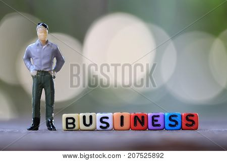 Businessman doll standing beside textbox of Business in concept of advertising publicity.