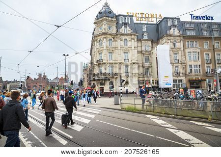 AMSTERDAM NETHERLANDS - JUNE 21 2016: Wide picture of the busy Damrak Street with many people a bicycle parking and hotels in a cloudy day. Amsterdam Netherlands.