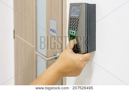 Young woman push down the electronic control machine to access the office door