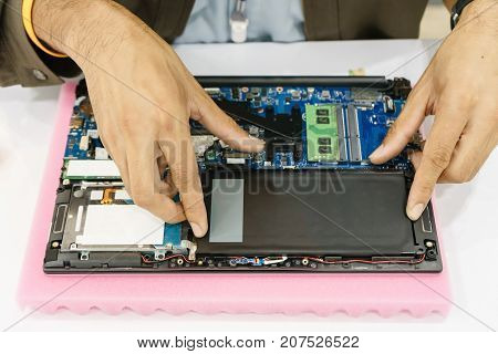 Laptop disassembling with screwdriver side view. Engineer fixing broken computer motherboard. Electronic repair shop technology development concept