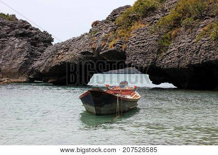 Old long-tail boat in the sea with natural stone bridge in the archipelago island Thailand.