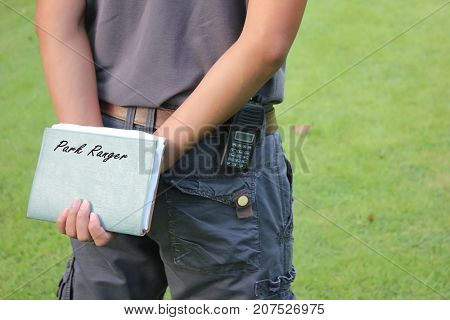 The notebook and radio of the park ranger in the garden.