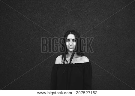 Girl portrait black and white on a dark background lots of free space look into the camera