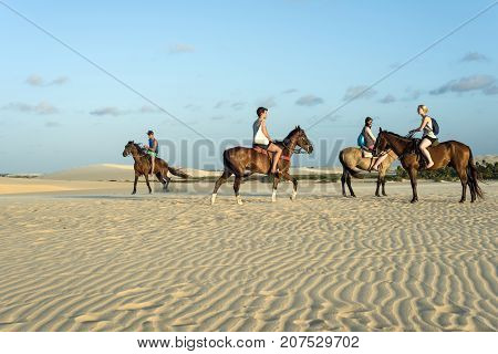 Jericoacoara Ceara state Brazil - July 18 2016: Tourists ride on horseback at Sunset Dune about an hour before sunset